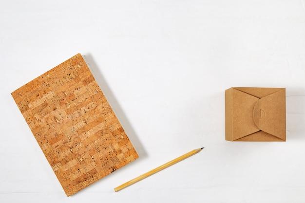 Quaderno chiuso a scuola, matita in legno e scatola artigianale sul tavolo. vista dall'alto con spazio di copia, fotografia piatta.