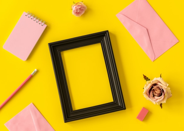 Quaderno dello spazio pastello e cornice nera con fiore rosa e matita su sfondo giallo