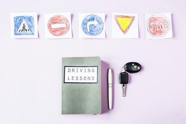 Quaderno di allenamento per lezioni di guida e regole del traffico di guida accanto ai disegni dei cartelli stradali per ottenere una patente di guida