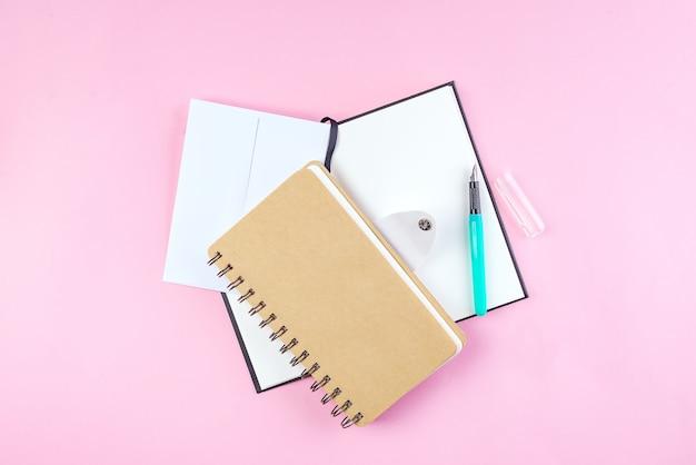 Quaderno di scuola su uno sfondo rosa, blocco note a spirale su un tavolo