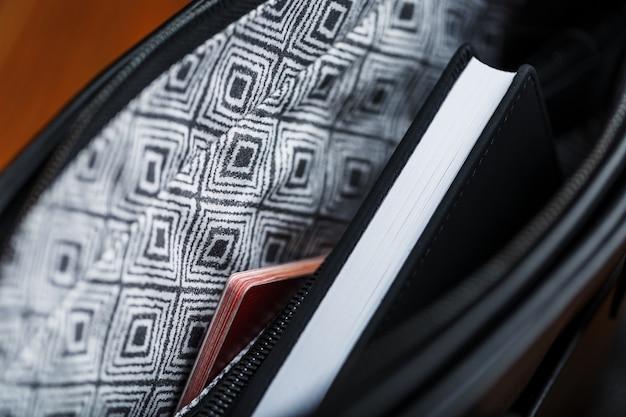 Quaderno nero che fa capolino dalla tasca di una borsa di pelle nera, macro, fatto a mano, materiali naturali.