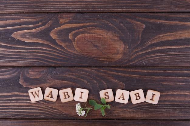 Quadrati di legno con lettere iscrizione wabi sabi. fondo in legno scuro copia spazio