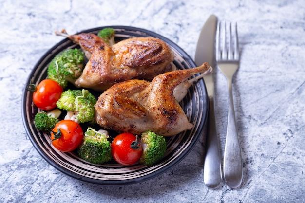 Quaglia fritta intera con broccoli e pomodorini. banda nera, fondo in marmo. messa a fuoco selettiva, da vicino.