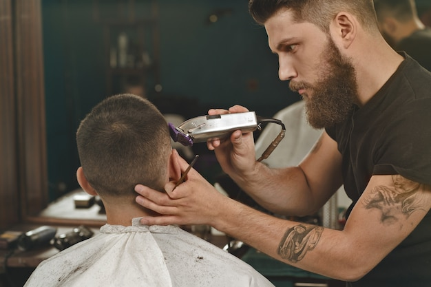 Qualche styling qui. colpo orizzontale di un bel barbuto e tatuato che dà un taglio di capelli al giovane che gli taglia i capelli