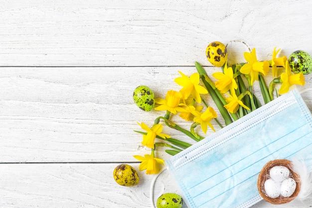 Quarantena di coronavirus durante le vacanze di pasqua. fiori di narciso di primavera con maschera medica viso e uova. modello