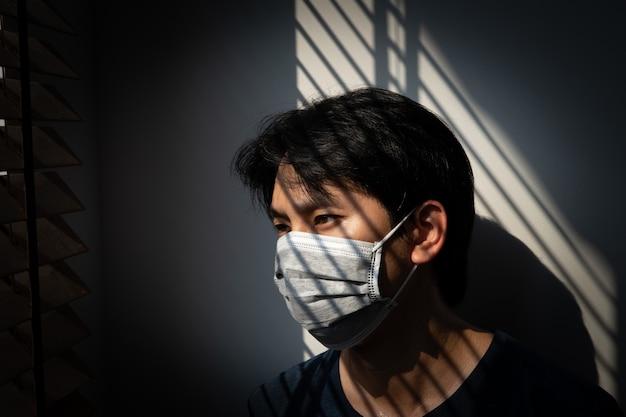 Quarantena di persone a rischio per prevenire la diffusione di covid-19, uomo che indossa una maschera e guardando fuori dalla finestra di casa, virus corona. sintomi e protezione di wuhan coronavirus e virus dell'epidemia
