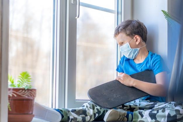 Quarantena domestica triste per bambini. ragazzo in maschera con skateboard si siede sul davanzale della finestra