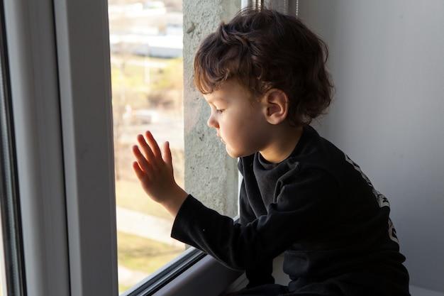 Quarantena durante una pandemia di coronavirus. . il bambino si trova sul davanzale della finestra e guarda la città vuota attraverso la finestra. sogna di uscire e respirare aria fresca.