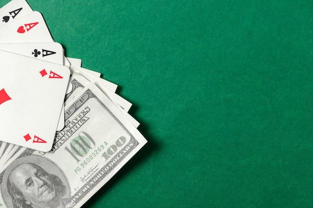 Quattro assi su uno sfondo verde con banconota da 100 dollari