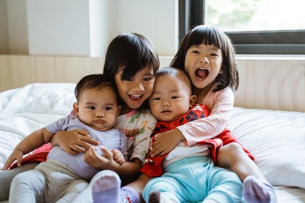Quattro bambini asiatici ridono seduti sul letto