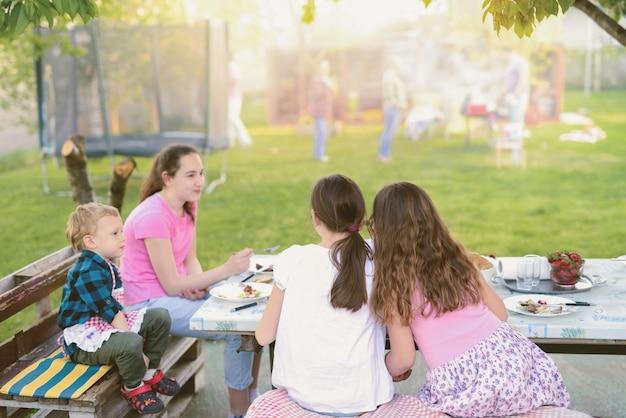 Quattro bambini seduti al tavolo in natura e mangiare.