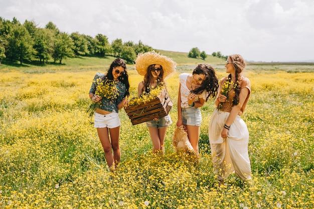Quattro bella ragazza hippie in un campo di fiori gialli