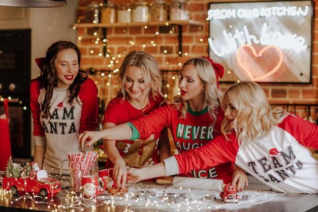 Quattro belle donne con i capelli ricci in pigiama invernale in posa in cucina