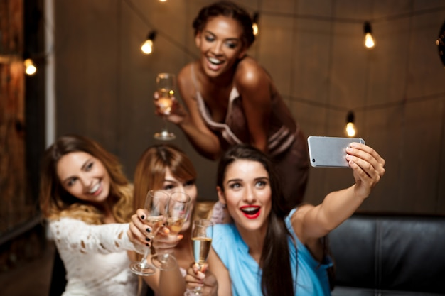Quattro belle ragazze che fanno selfie alla festa.