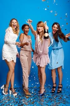 Quattro belle ragazze che riposano alla festa sopra la parete blu