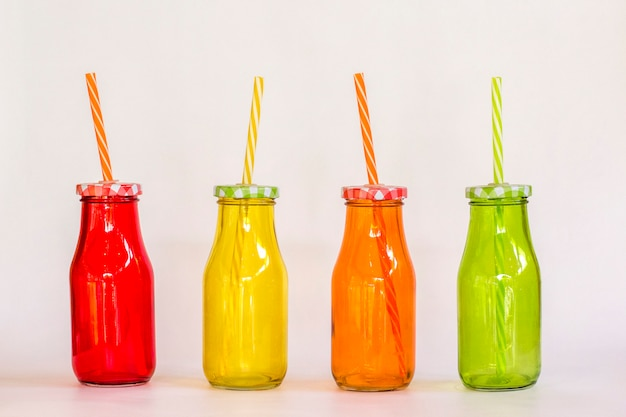 Quattro bottiglie di vetro colorate per cocktail con coperchio e supporto di paglia in fila
