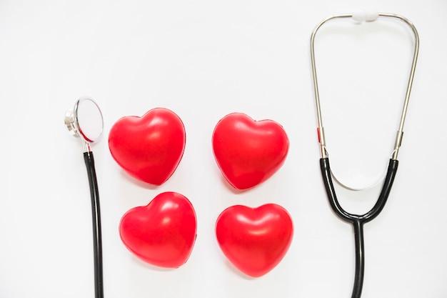 Quattro cuori rossi con stetoscopio su sfondo bianco