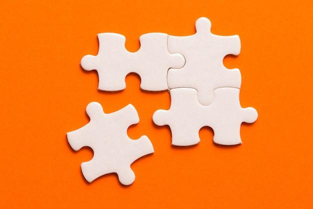 Quattro dettagli bianchi del puzzle su sfondo arancione