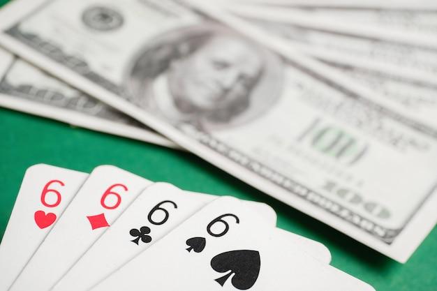 Quattro di sei durante il poker con dollari sul tavolo verde.