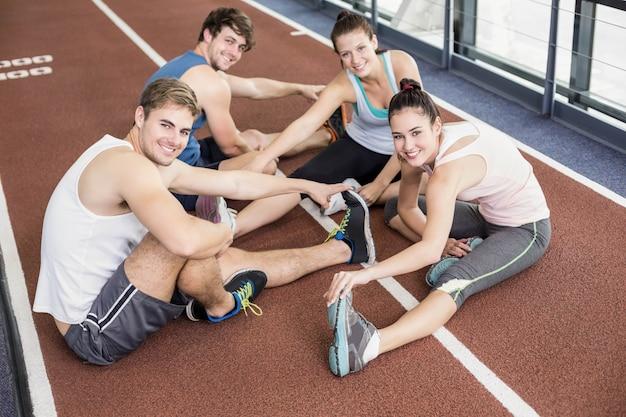 Quattro donne e uomini atletici che si allungano sulla pista da corsa
