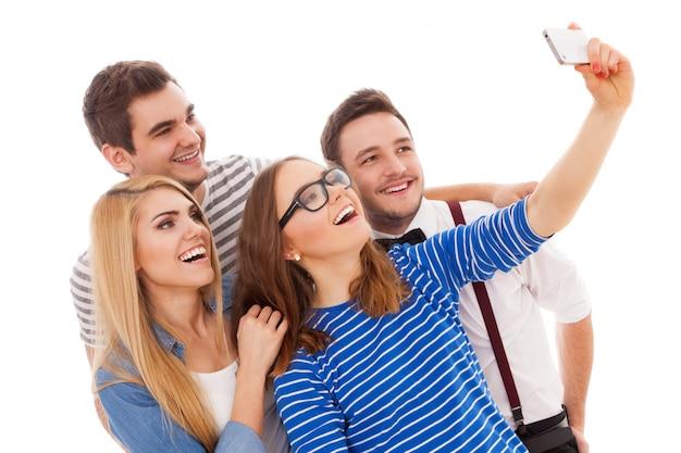 Quattro giovani alla moda su sfondo bianco