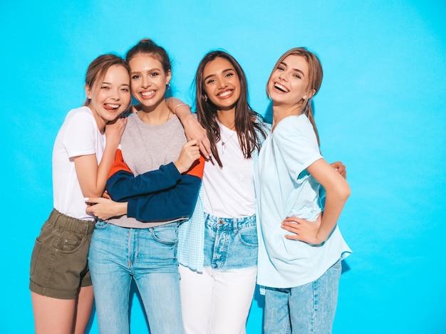 Quattro giovani belle ragazze sorridenti hipster in abiti estivi alla moda. donne spensierate sexy che posano vicino alla parete blu in studio. modelli positivi che si divertono e si abbracciano