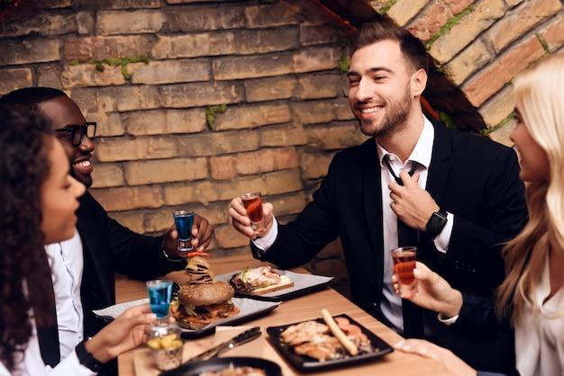 Quattro giovani bevono alcolici in un bar.