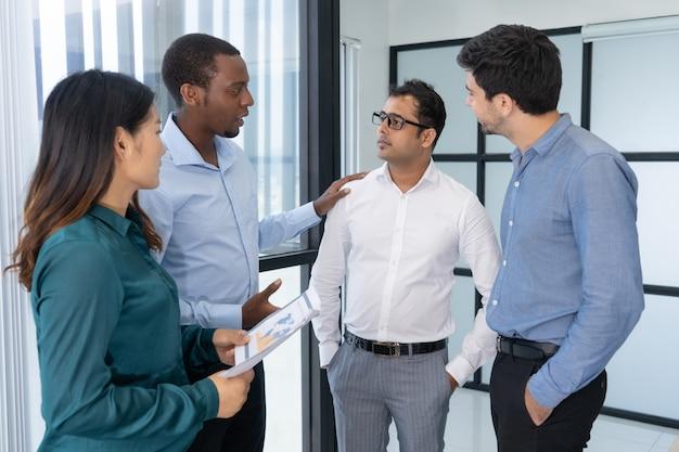 Quattro giovani uomini d'affari che discutono la strategia di negoziazione prima di incontrare i partner