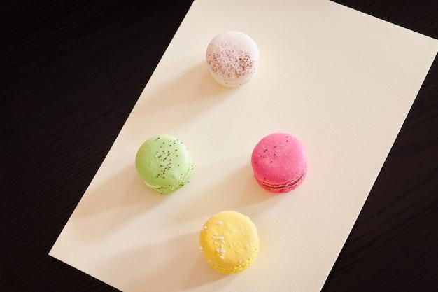 Quattro macarons multicolori su un foglio di carta gialla