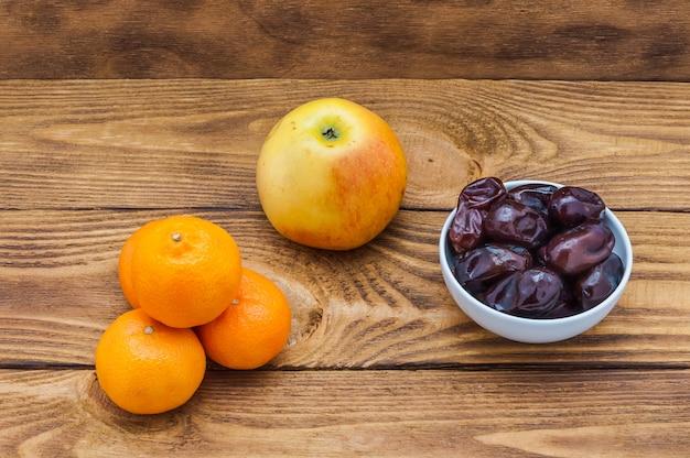 Quattro mandarini maturi arancione brillante, una mela e una tazza con le date su una tavola di legno.