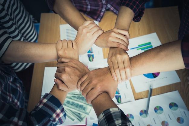 Quattro mano insieme in riunione d'affari per il concetto di squadra