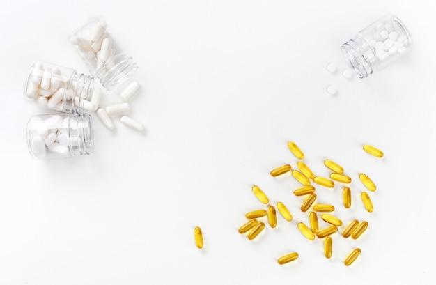 Quattro pacchetti con varie pillole bianche e compresse d'oro su uno sfondo bianco. concetto di salute. vista dall'alto con spazio di copia.