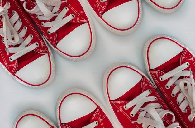 Quattro paia di scarpe da ginnastica rosse su una superficie di legno bianca