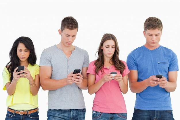Quattro persone in piedi l'una accanto all'altra e mandare sms ai loro telefoni