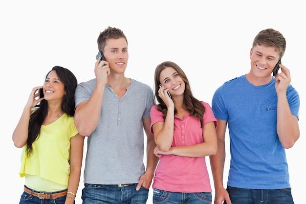 Quattro persone su tutti i loro telefoni mentre stanno uno accanto all'altro
