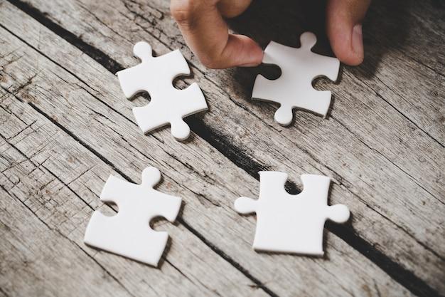 Quattro pezzi di puzzle bianco su legno