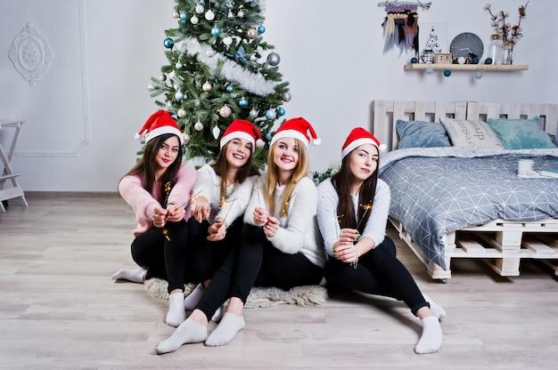 Quattro ragazze carine di amici indossano maglioni caldi, pantaloni neri e cappelli rossi di babbo natale contro l'albero con decorazioni natalizie in camera bianca