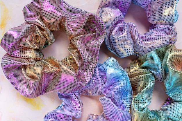 Quattro scrunchies metallici lucidi iridescenti alla moda olografici sul tavolo rosa