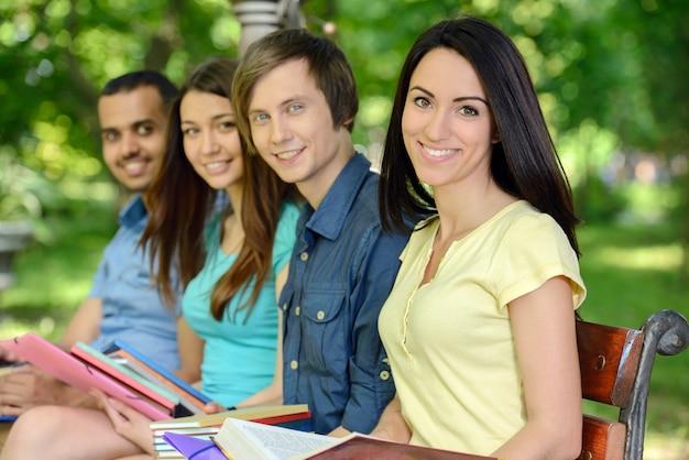 Quattro studenti allegri sorridenti all'aperto nel parco.