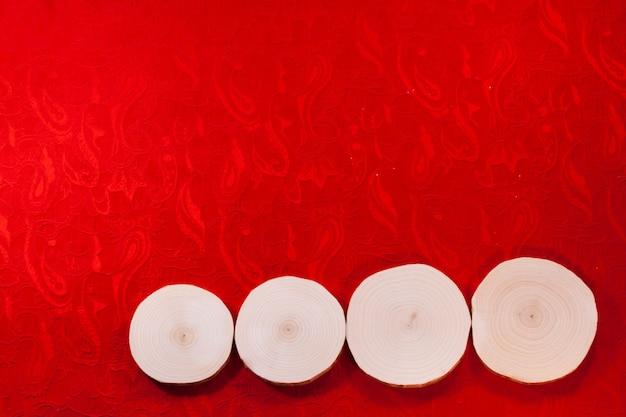 Quattro tagli di sega d'ontano su un bel tessuto rosso decorato.