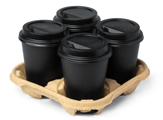 Quattro tazze di caffè asportabili nere in un vassoio su bianco