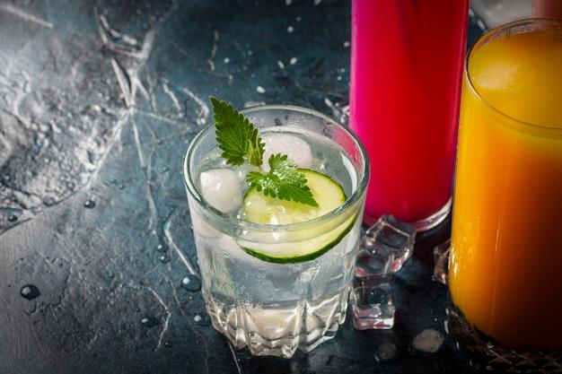 Quattro tipi di bevande rinfrescanti con ghiaccio su una superficie blu scuro e cubetti di ghiaccio.