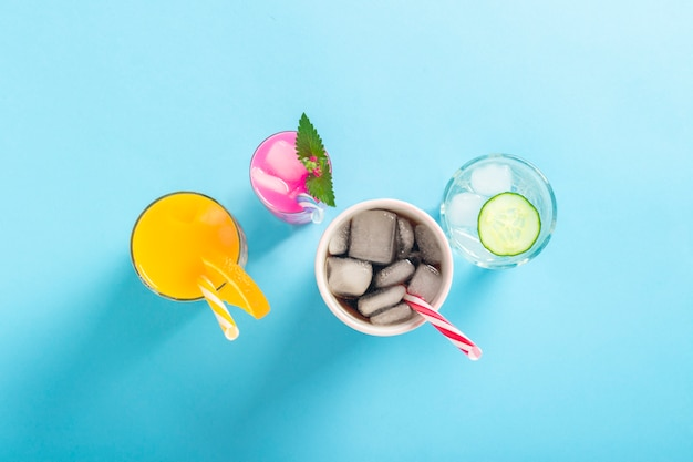 Quattro tipi di bevande rinfrescanti con ghiaccio su una superficie blu scuro. vista piana, vista dall'alto
