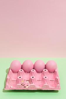 Quattro uova di pasqua rosa in grande rack sul tavolo verde