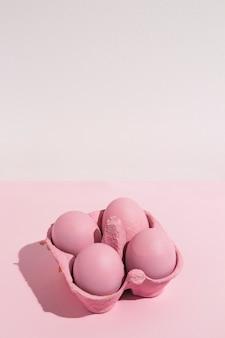 Quattro uova di pasqua rosa in rack sul tavolo luminoso