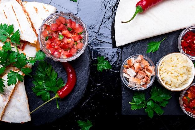 Quesadilla messicana ed ingredienti con salsa sul piatto nero della pietra dell'ardesia