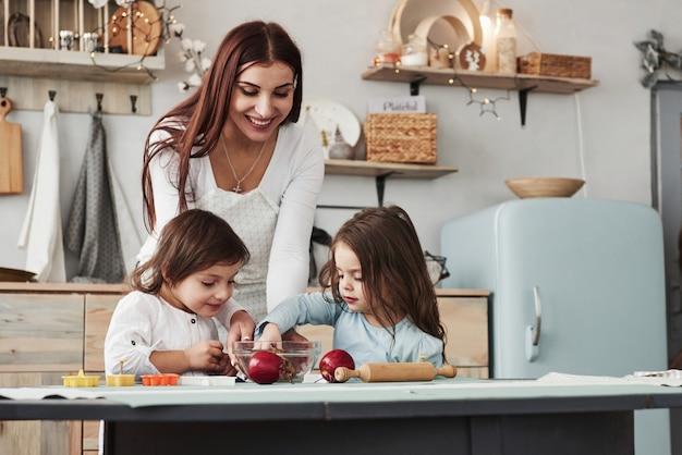 Questa ragazza ha preparato il cibo appositamente per loro. la giovane bella donna dà i biscotti mentre si siedono vicino al tavolo con i giocattoli
