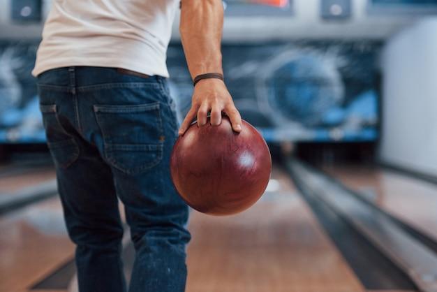 Questo sarà lo sciopero. vista posteriore delle particelle dell'uomo in abiti casual che giocano a bowling nel club