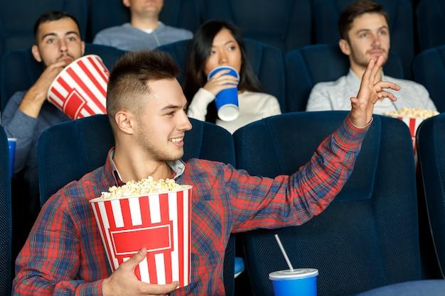 Qui. giovane uomo casual agitando la mano verso l'amico mentre era seduto al cinema a godersi film