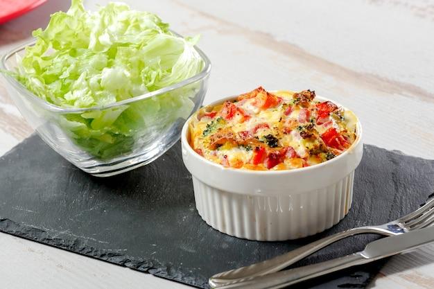 Quiche con broccoli, formaggio e pomodori, insalata di fondo